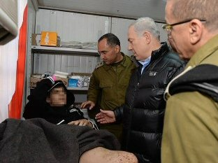 Ministerpräsident Netanyahu im Gespräch mit eine syrischen Verletzten (Foto: GPO)