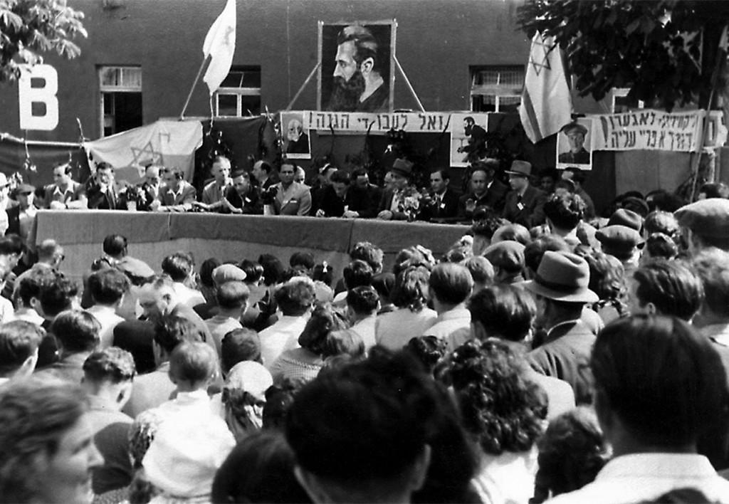 """In der Ulmer Boelcke-Kaserne fordern die Juden freie Einwanderung nach Erez Israel. """"Sol lebn di Hagana!"""" ist unter dem großen Herzl-Portrait zu lesen. Repro: nurinst-archiv"""