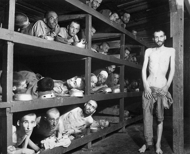 Sklavenarbeiter im KZ Buchenwald nahe Jena; viele waren an Unterernährung gestorben, als U.S. Truppen der 80th Division das Lager betraten. Der sehr kranke Mann auf dem Rücken im unteren Stockbett ist Max Hamburger, der an TBC und schwerer Unterernährung litt. Er konnte sich erholen und wurde Psychiater in den Niederlanden. In der zweiten Reihe, siebter von links liegt Elie Wiesel. Aufnahme 5 Tage nach der Befreiung. Date16 April 1945 Source U.S. Defence Visual Information Center, image #HD-SN-99-02764; NARA image ARC #535561, file #208-AA-206K(31).