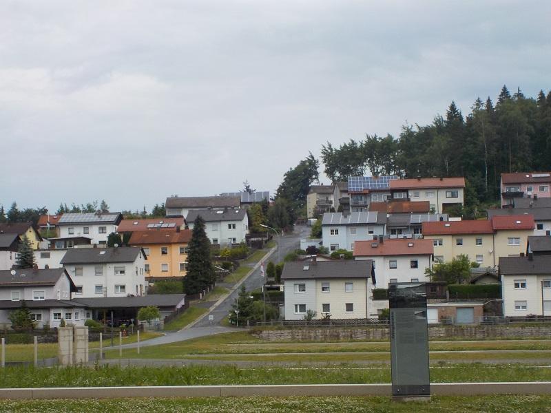 Die Siedlung auf ehemaligem KZ-Grund. Im Bild oben, kurz nach der Befreiung von amerikanischem Militär aufgenommen, sind die Baracken am Hang zu sehen. (C) Eva von Steinburg
