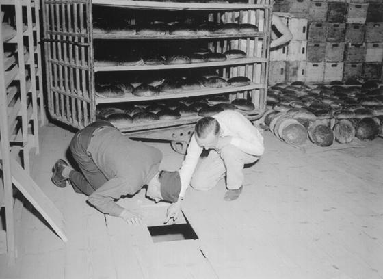 Ein US-Leutnant (links) und ein deutscher Kriminalbeamter inspizieren die Bäckerei und das Versteck von Leipke Distel. Foto: Public Domain (US National Archives)